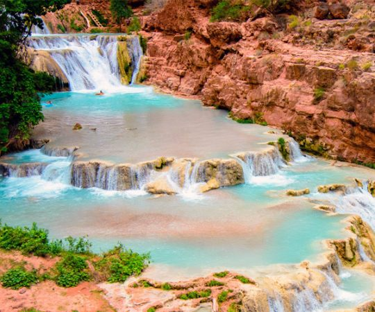 Pools of turquoise water cascade into falls below