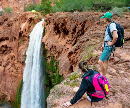 A man and woman stand at the edge of a cliff overlooking a waterfall. Tents and trees can be seen in the background