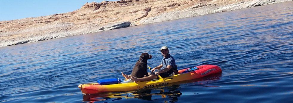 A man kayaks on Lake Powell with his dog.