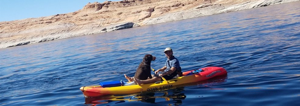A man kayaks on Lake Powell with his dog.