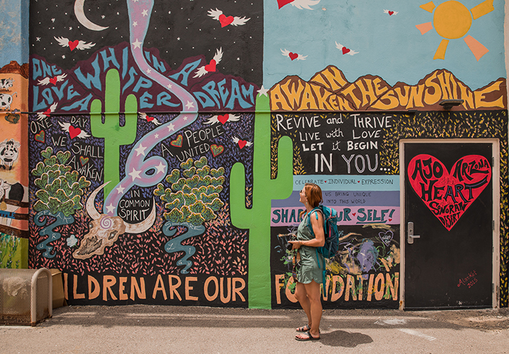 A woman in front of a cactus mural in Ajo Arizona