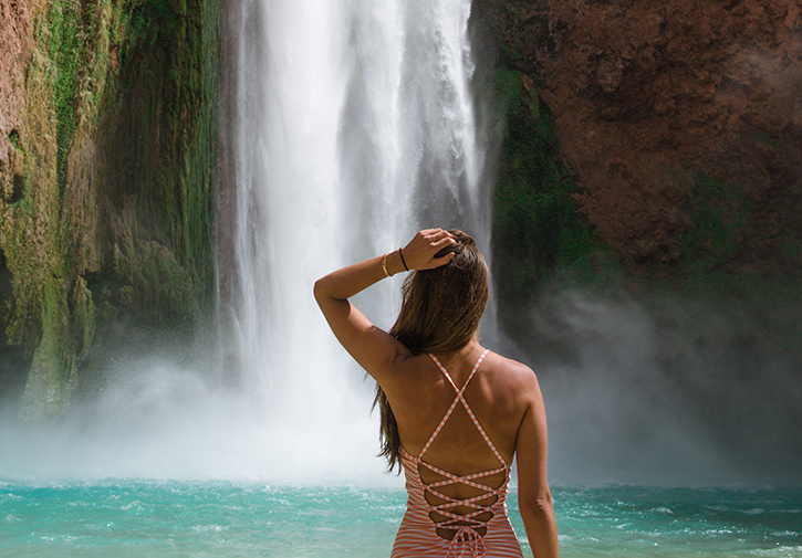 Woman stands at the base of a waterfall with her back to the camera.