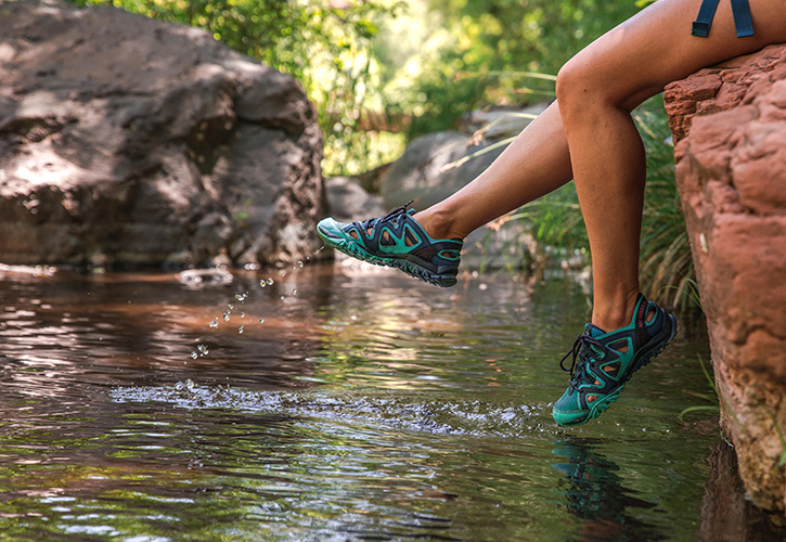 Legs dangle over a lake in hiking shoes.