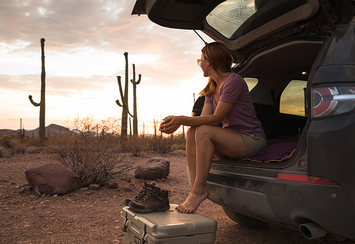 A woman sits in the tailgate of a black SUV in an Arizona desert.