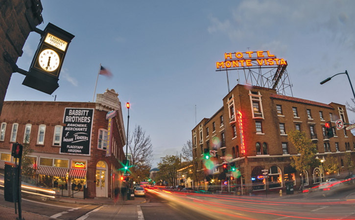 Dusk on a busy downtown street in a small town. Neon signs are on, one advertising the Hotel Monte Vista.