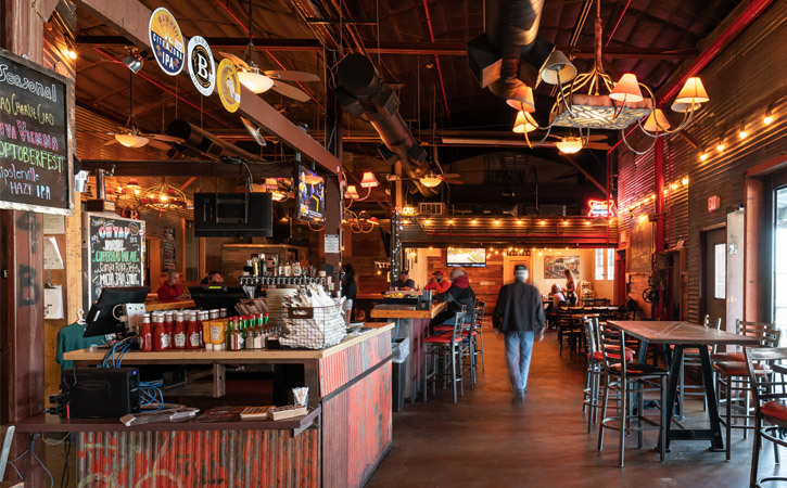 Interior of an industrial-style brewery and restaurant. A man walks away, in between a row of tables.