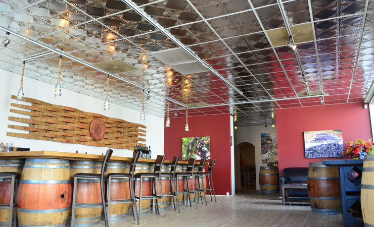 A bright and airy tasting room with tin-square celiengs and barrels as decor