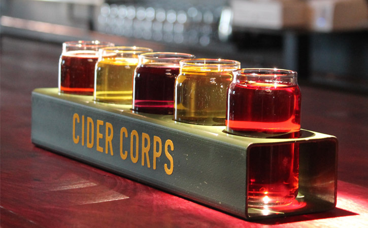 A row of glasses with different colored ciders (yellow, pink and red) in a green tray with the words 'Cider Corps'