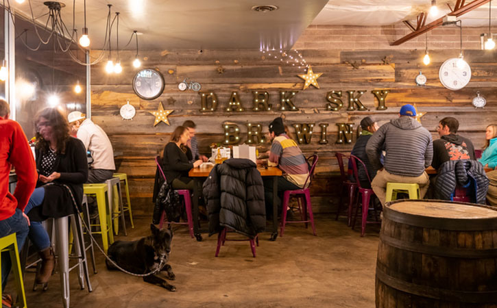 People sitting at tables, chatting and drinking inside Dark Sky Brewery in Flagstaff