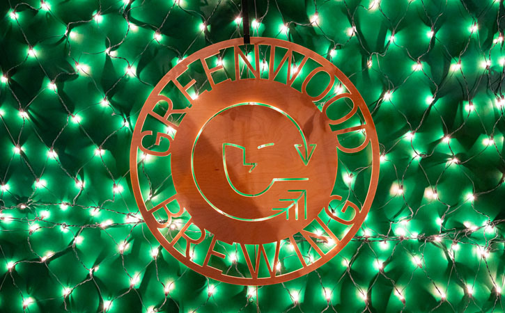 Green Christmas lights illuminate a brass sign with the logo of Greenwood Brewing