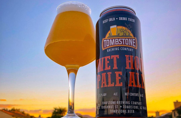 A can of Tombstone Brewing Co pale ale stands next to a glass of the same ale. The sunset sky serves as the background