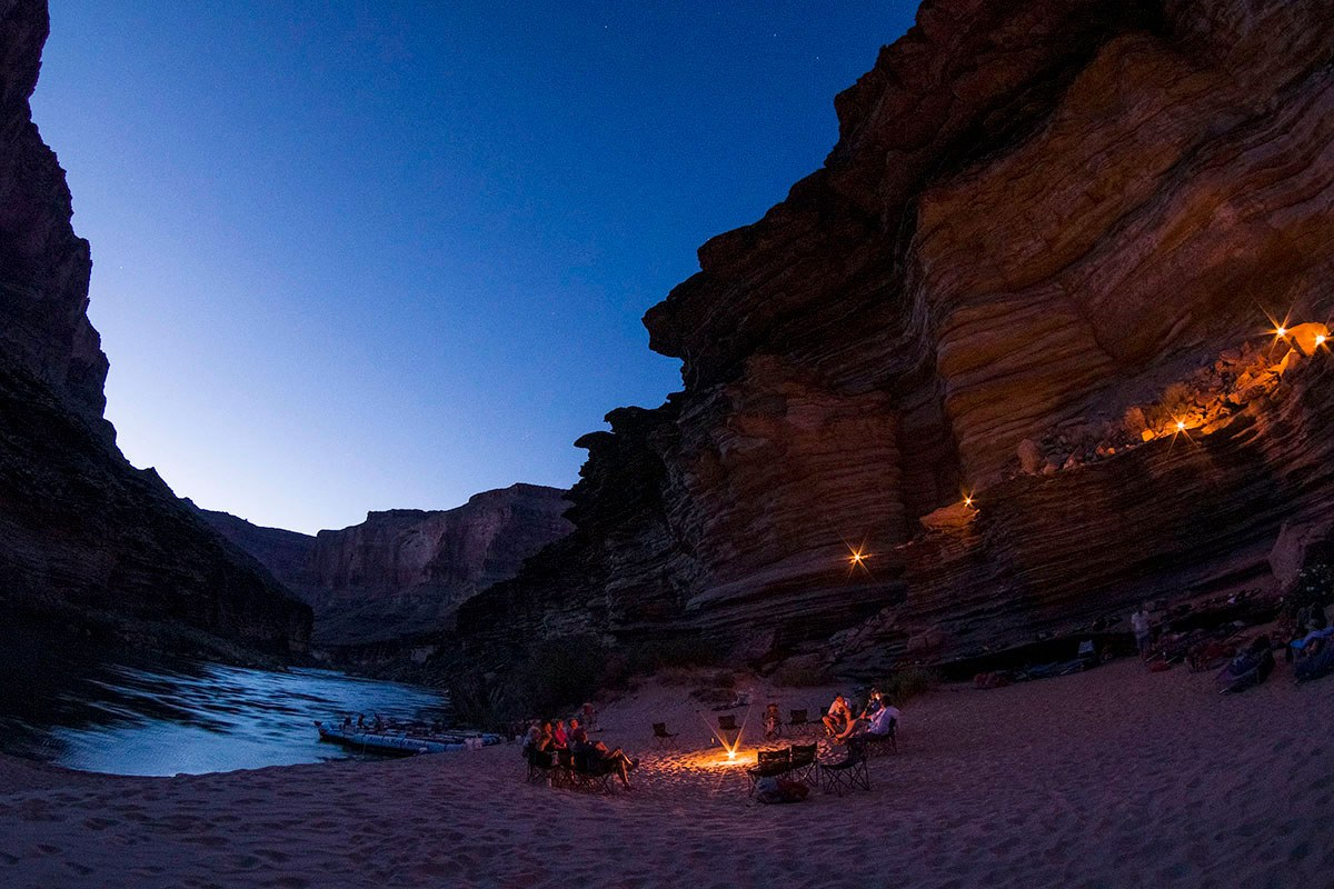 After a day of white-water rafting on the Colorado River, rafters relax beachside and prepare to camp for the night