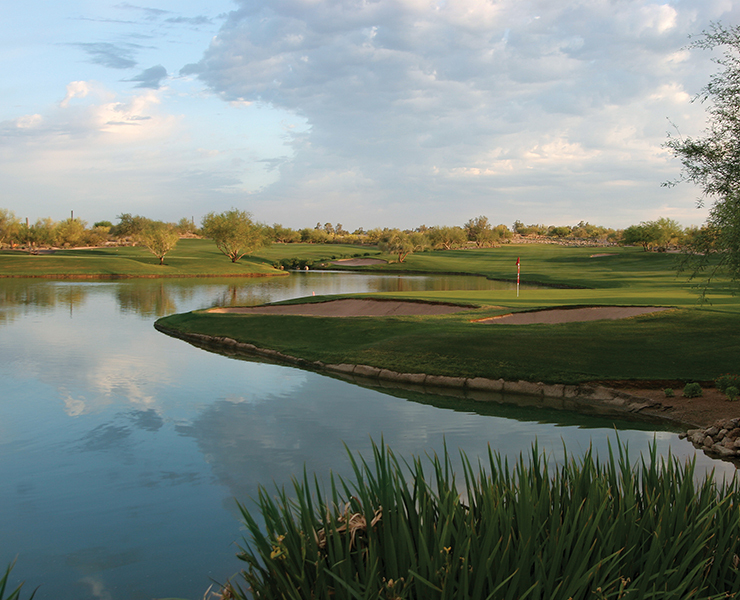 Golfers on the 18th hole of Grayhawk Golf Club's Raptor Course which features sloping greens and a water hazard