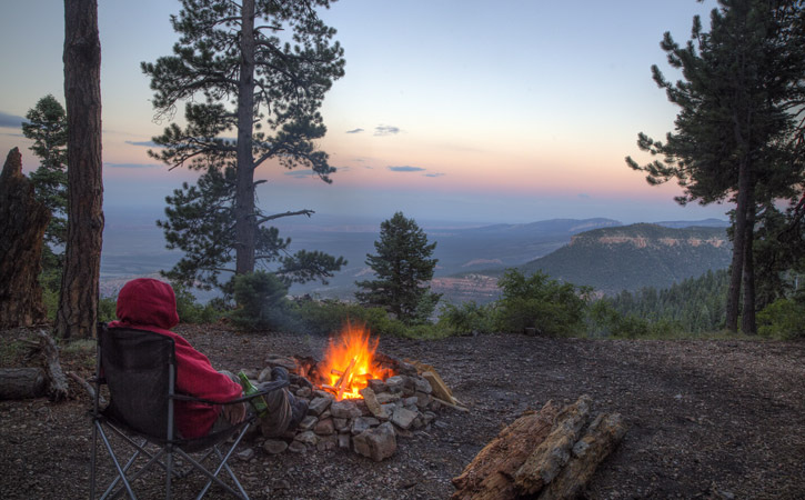 A man sits near a small campfire overlooking the Grand Canyon