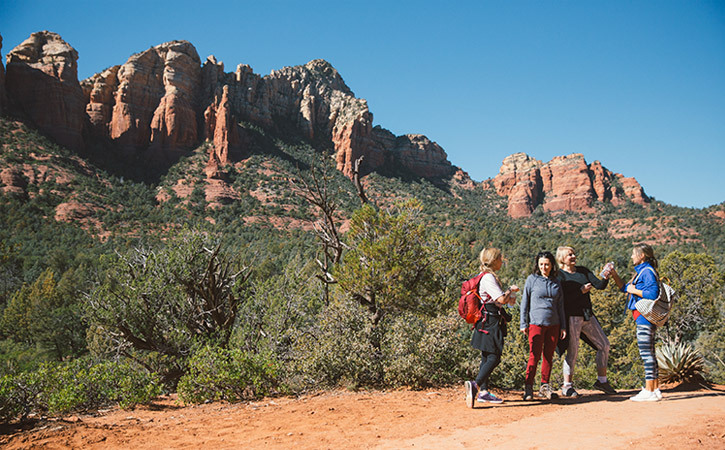 A group of women chat on a desert trail beside a landscape of red rocks