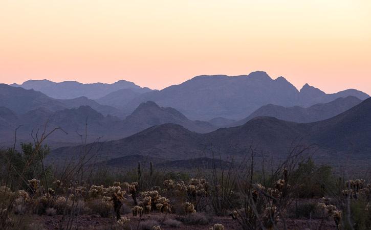 Purple mountain ranges under a yellow-orange sky