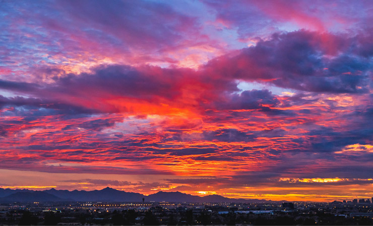Purple, orange, pink and blue-hued clouds fill the sky at sunset over South Mountain in Phoenix