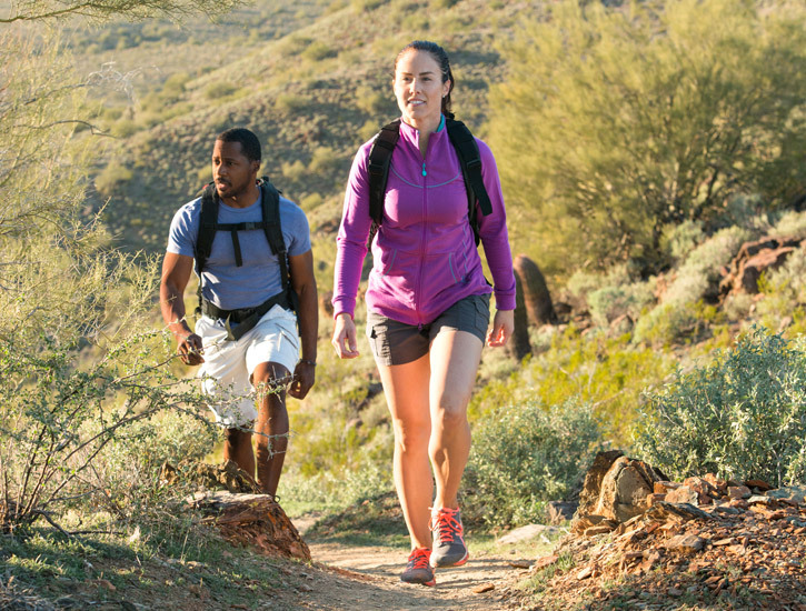 A man and woman hike outside on a desert trail