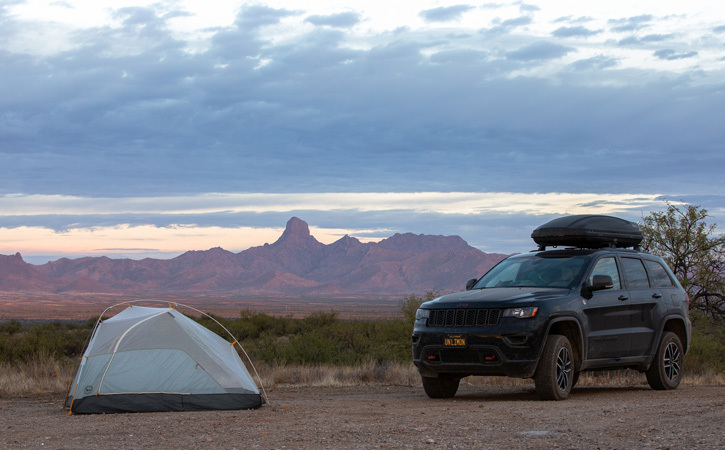 An SUV and a white tent sit in the foreground, while in the back, the peaks of a mountain range can be seen under a cloudy sky.