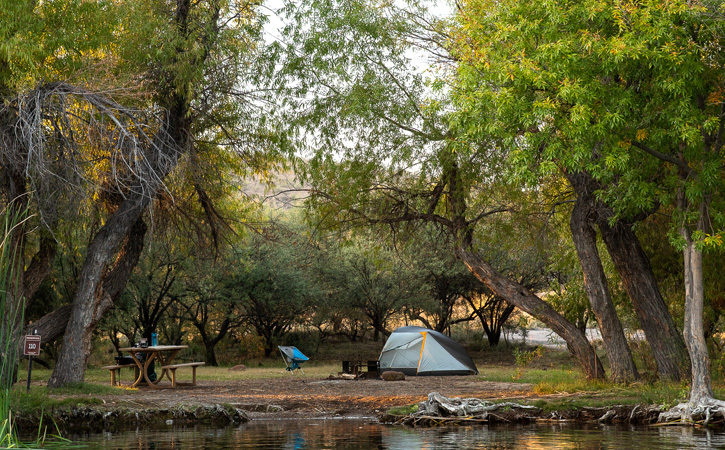 A tent sits near a lake and surrounded by trees.
