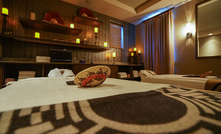 A warmly lit spa room with candles and American Indian decor