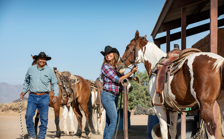 A woman smiles as she gets holds the reins of a horse. A cowboy walks with his horse behind her.