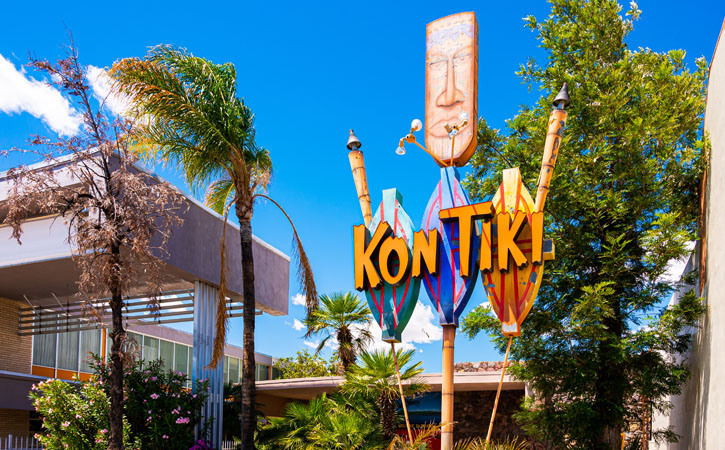 A large sign saying 'kon-tiki' in a Polynesian style stands outside a nondescript set of building next to several palm trees