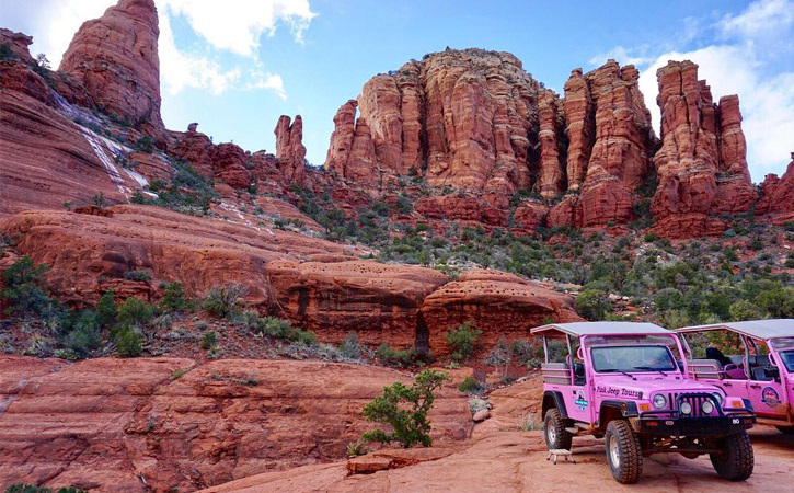 Two pink Jeeps on a plateau, in a valley surrounded by Sedona's red rock mountains