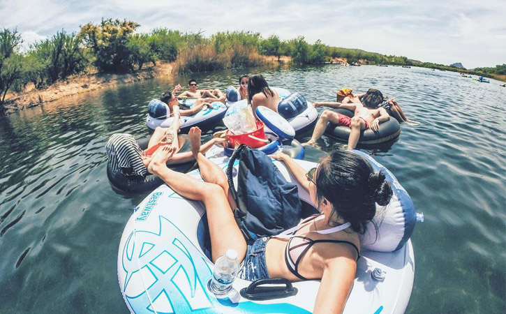 A group of friends hang out on the water in inner tubes.