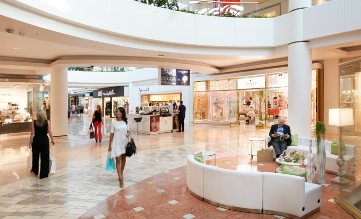 Shoppers walk through a bright and airy shopping mall