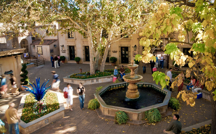 Groups of people walk in an open-air, Spanish-style plaza; a fountain and several trees sit in the center