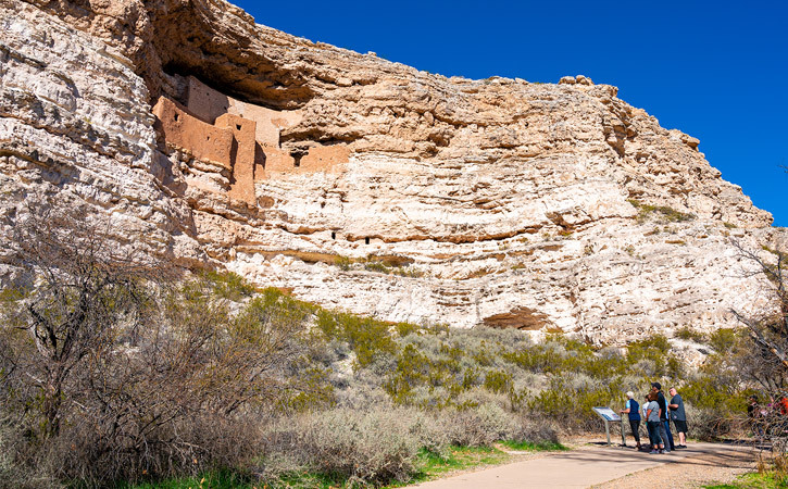 A group of people stand by a sign on a paved trail in front of ancient ruins carved into a giant rock wall