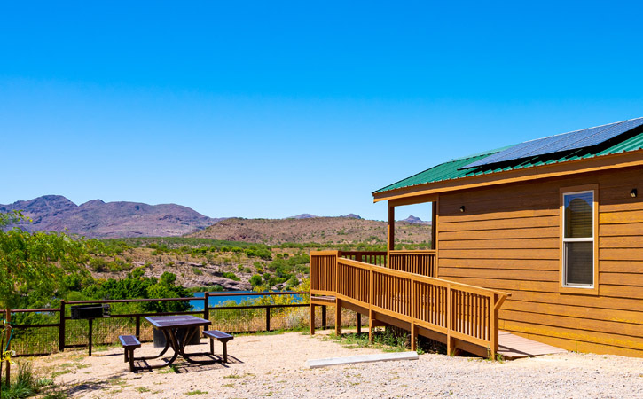 A wood cabin and metal picnic table overlook a landscape with a view of a lake, mountains and desert greenery