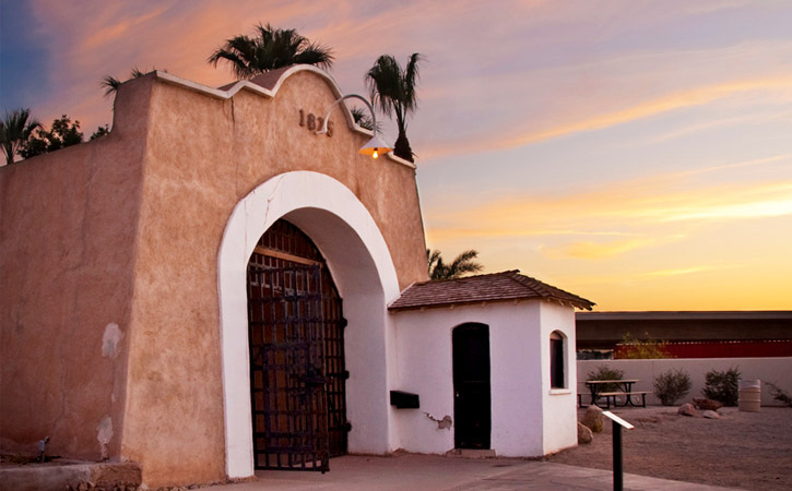 A historic, Spanish Mission-style building sits underneath a sunset-filled sky