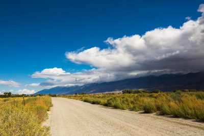 image of dirt road with mountains and clouds