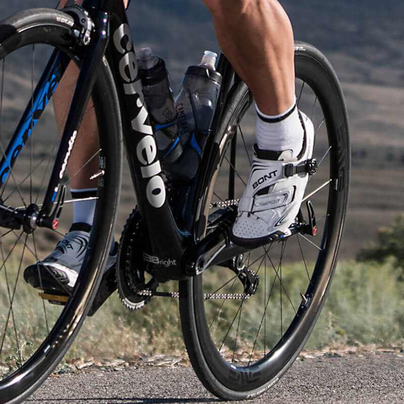 Close up of man's feet on pedals of road bike.