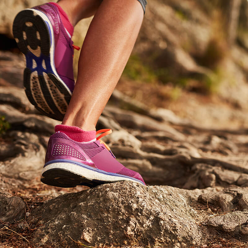 Close up of woman's feet in pink running shoes on rocky trail