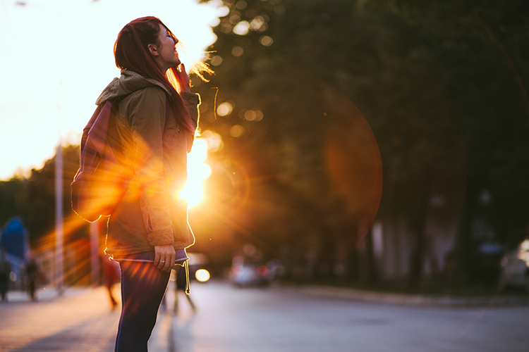 Female Walking In Sunlight With Smile On Her Face