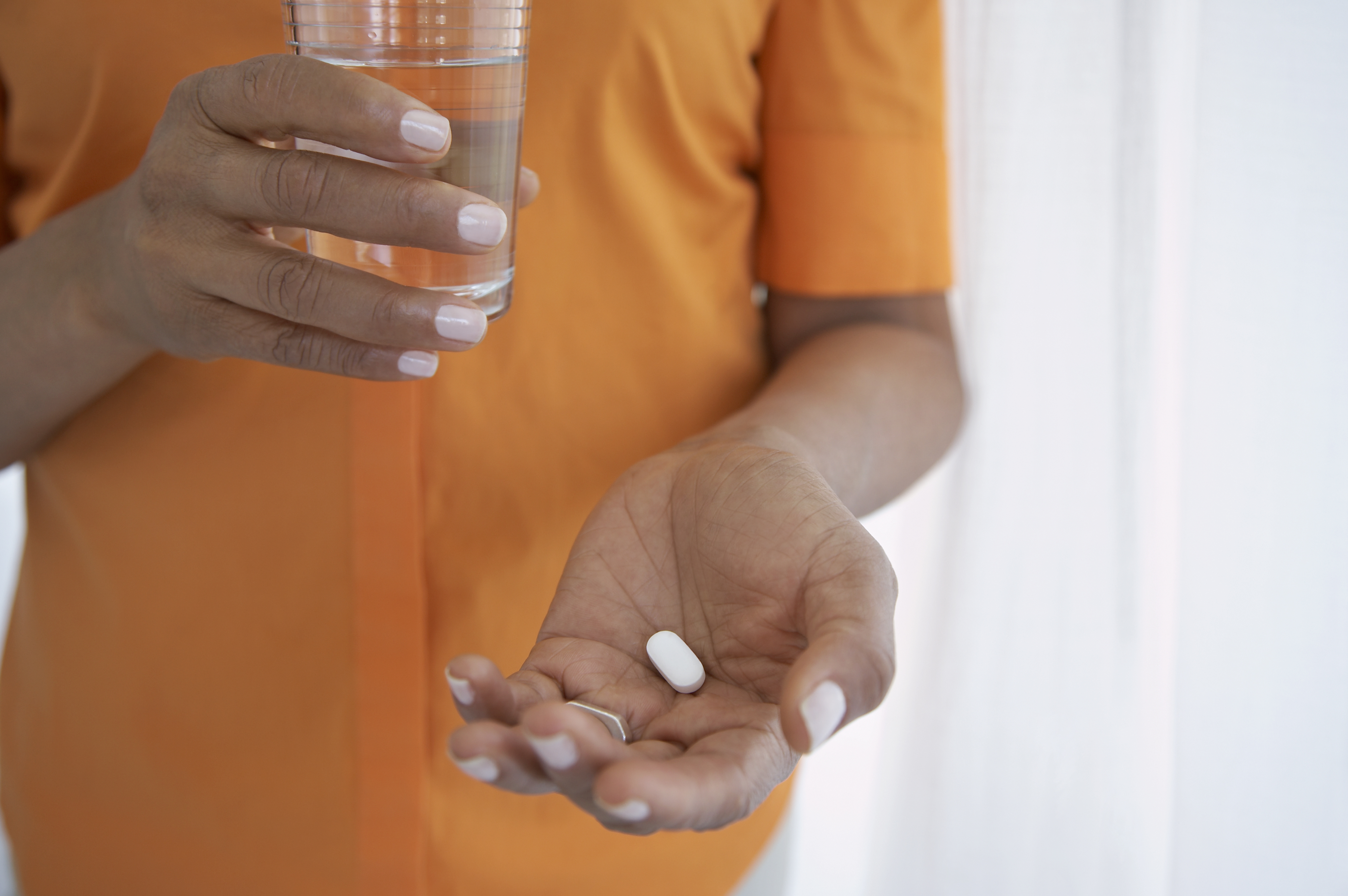 female hands with pill.