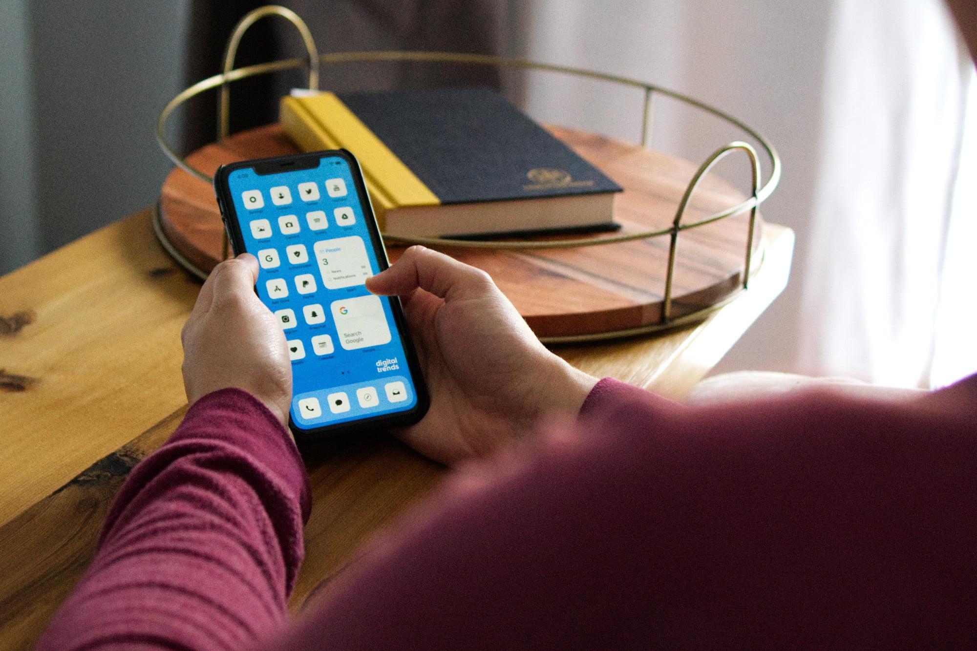 Persona que tiene un iPhone 11 con un diseño de pantalla de inicio personalizado.