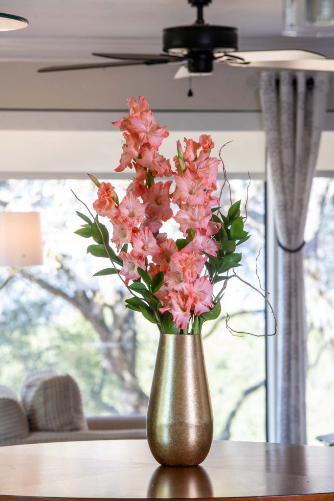 Coral-colored Gladiolus cut flower arrangement in a vase in front of a window