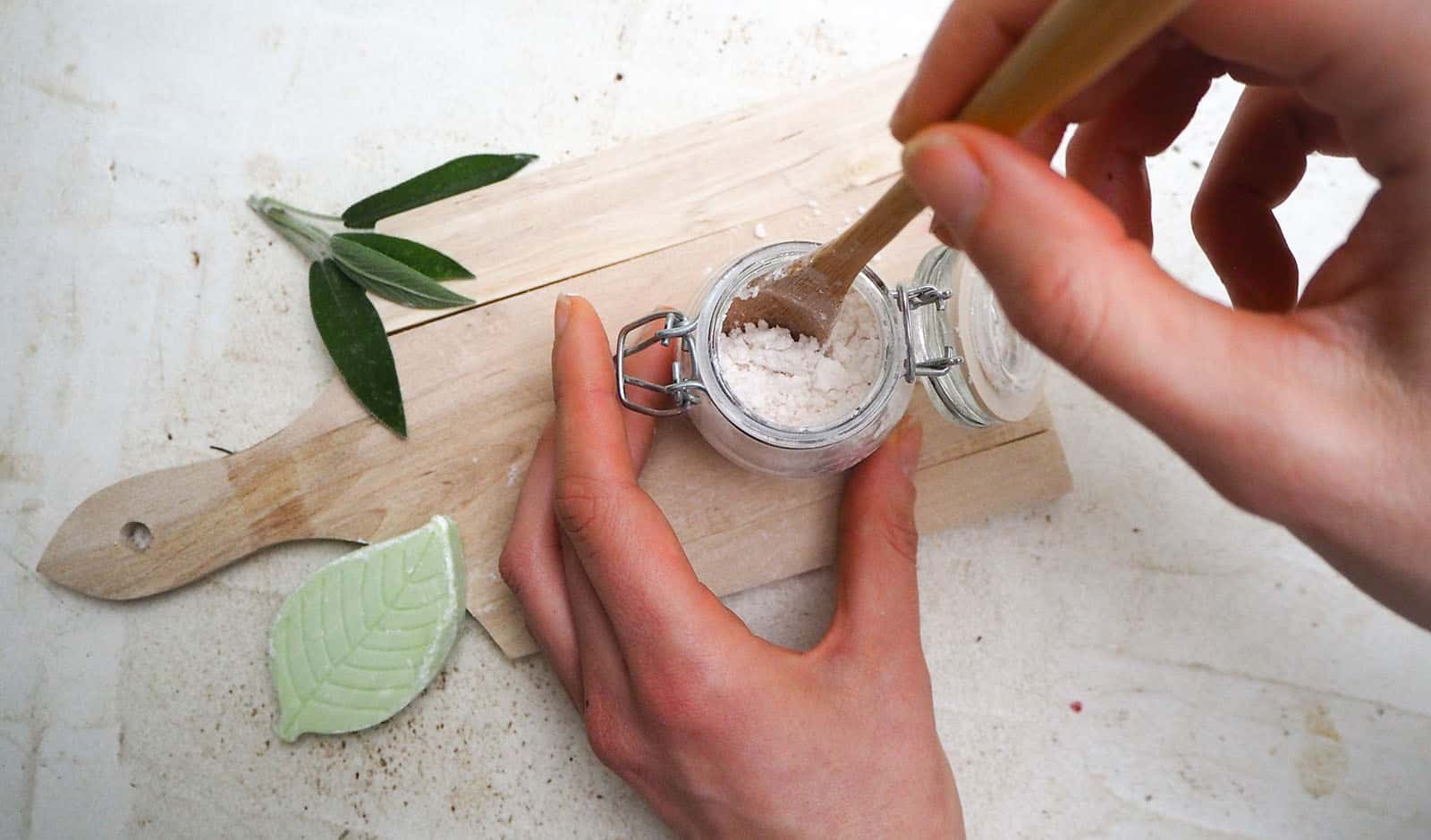 Caucasian woman making homemade vegan deodorant in a glass jar a