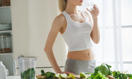 woman-in-kitchen-drinking-water-from-a-glass