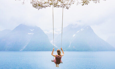 woman-on-swing-hanging-above-the-water-with-mountains-in-background-peaceful-serene-beautiful