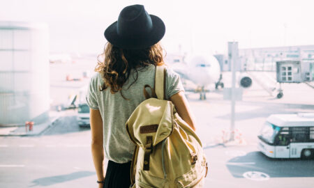 woman-staring-at-plane-with-packed-backpack