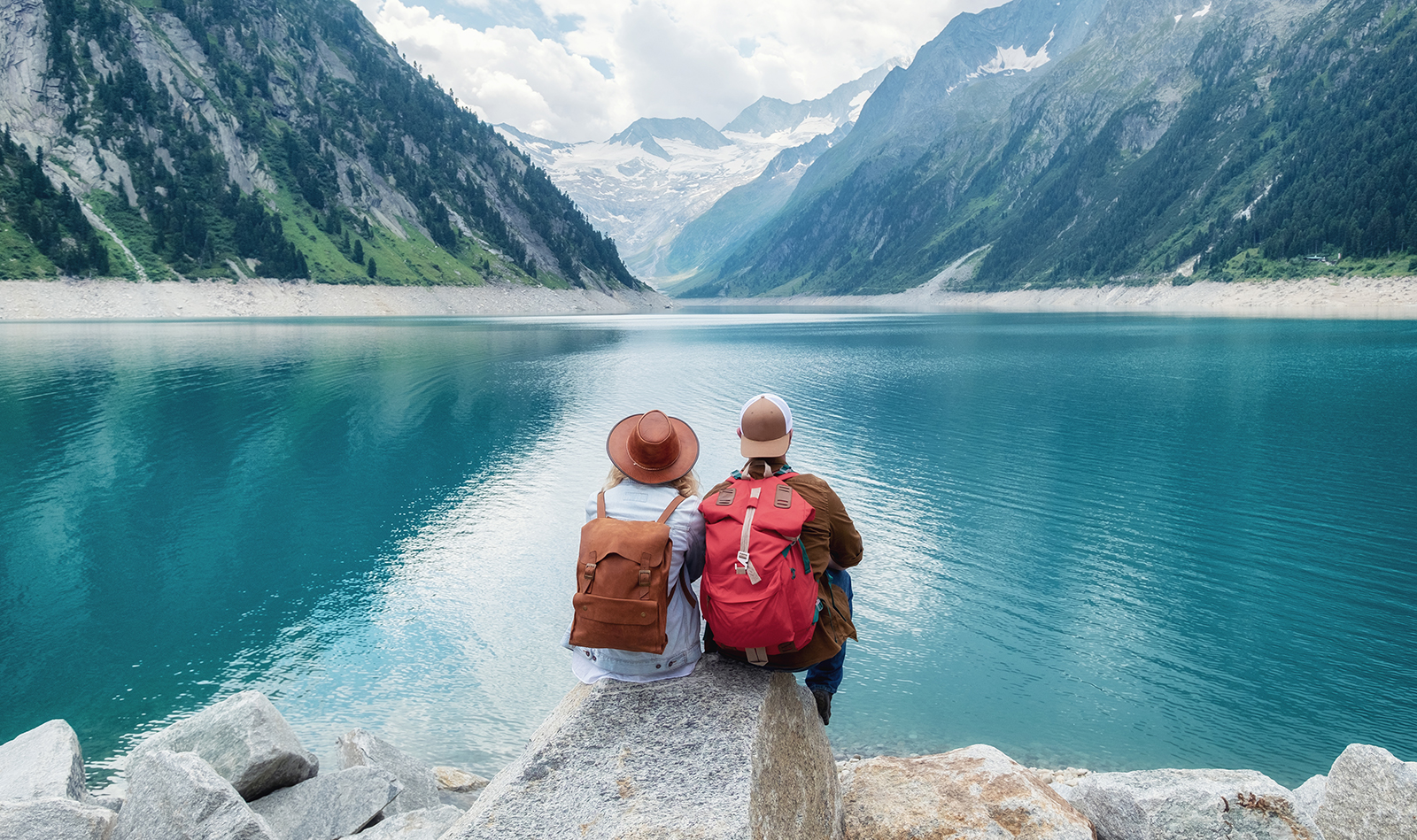 couple-traveling-together-sittin-in-front-of-mountains-and-sea