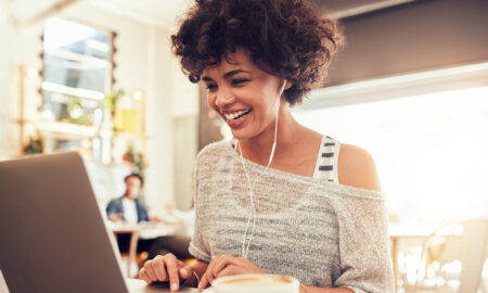 woman-on-computer-smiling-beautiful-natural-hair