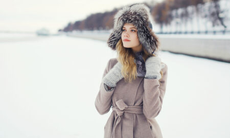 winter-fashion-girl-in-fluffy-hat-glvoes-and-coat-in-snow