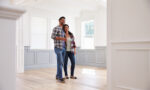couple-looking-at-walls-inside-empyt-house-home-home-improvement