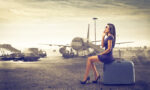 travel-woman-sitting-on-suitcase-in-front-of-plane